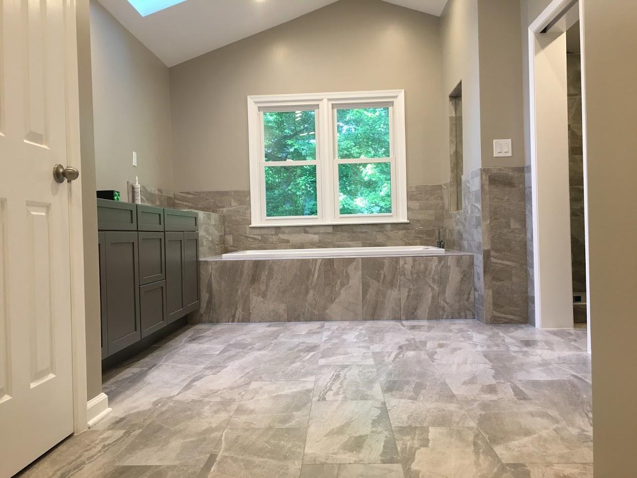 bathroom entryway flooring and bath tub with wooden cabinets