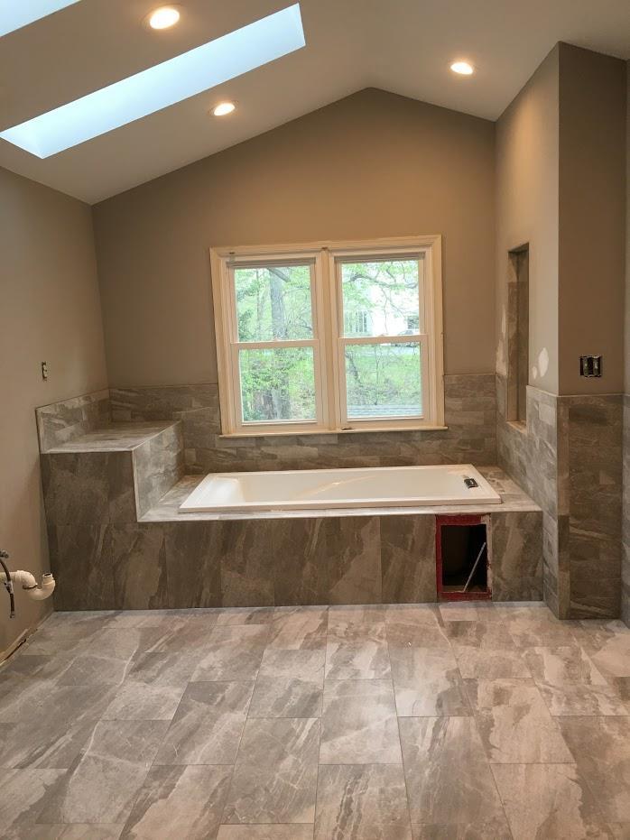 bath tub installation near window with modern lighting