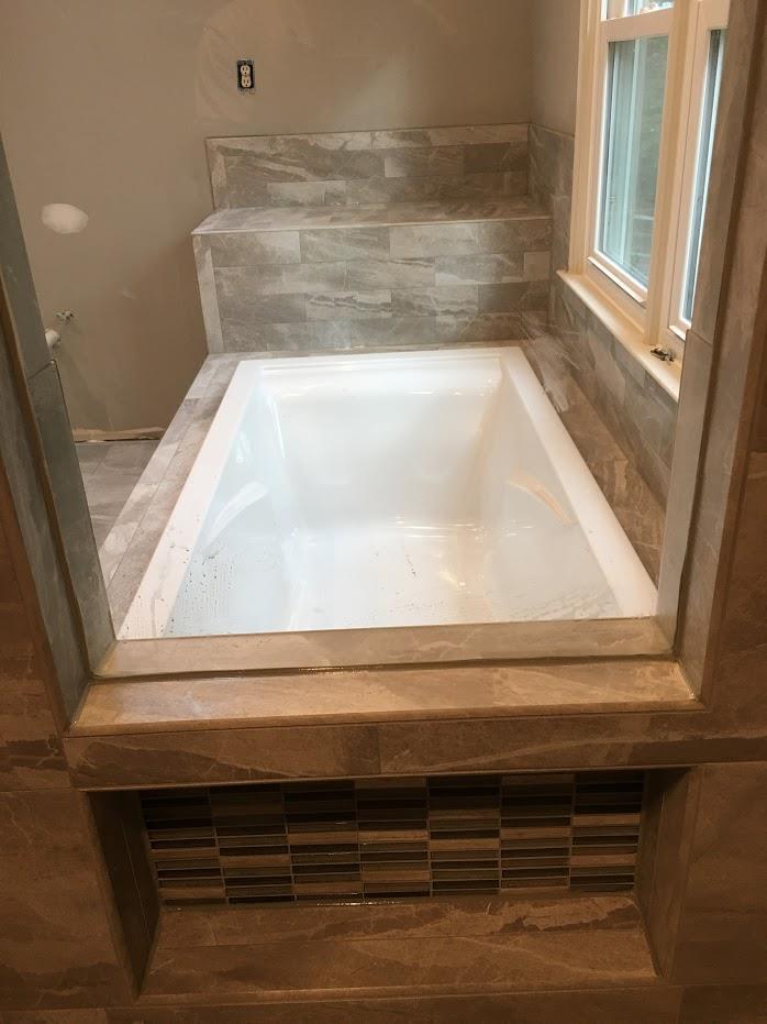bath tub installation with stone tiles
