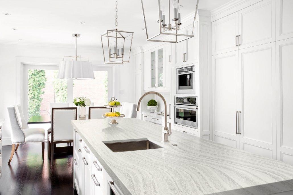 Spectrum Quartz Countertop Stone in a classic all-white kitchen design with wall lamp
