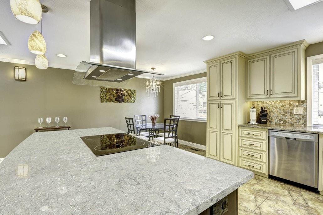 Spectrum Quartz Countertop Stone with cream kitchen cabinets and elegant lighting